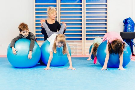 Group of children  exercising with fitness balls