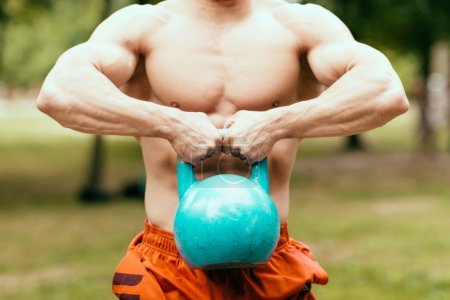 Photo for Muscular crossfit athlete exercising with kettle bell - Royalty Free Image