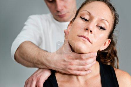 Photo pour Chiropraticien examinant le cou d'une patiente - image libre de droit