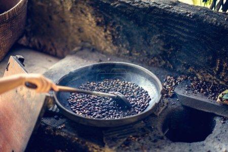 senior hand roasting coffee on civet