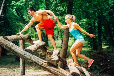 muscular couple exercising on fitness trail