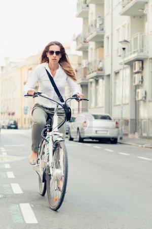 female office worker riding e-bike