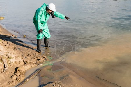 Environmentalist pointing to polluted water