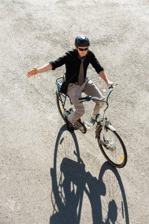 Photo pour Homme d'affaires à cheval sur un vélo électrique, signalisation avant de tourner à droite - image libre de droit