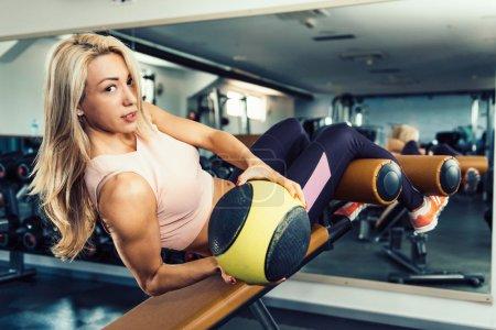Photo pour Athlète féminine exercer avec médecine-ball et regardant la caméra - image libre de droit
