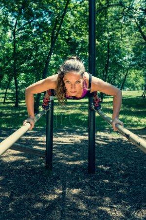 athlete doing push-ups on bars