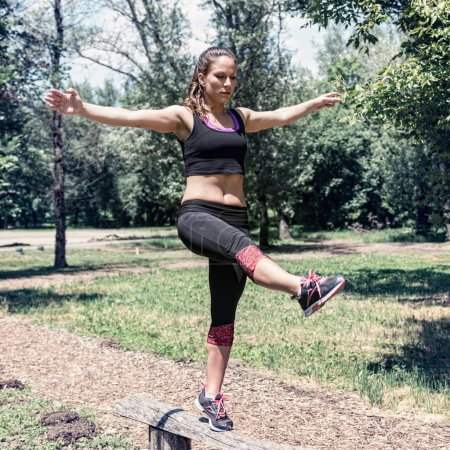 Female balancing on wooden barrier