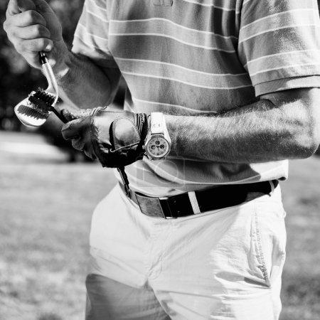 Golfer cleaning iron golf club