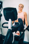 blond woman using gym bicycle