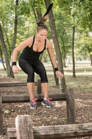 Photo for Female crossfit athlete crossing hurdles on fitness trail - Royalty Free Image