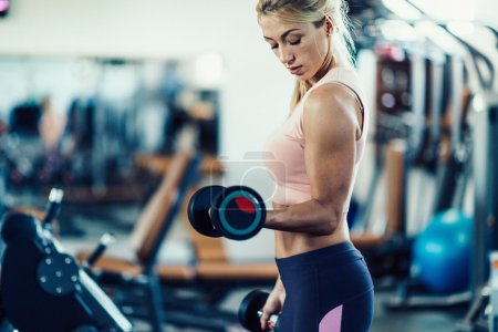 woman exercising with weights in gym