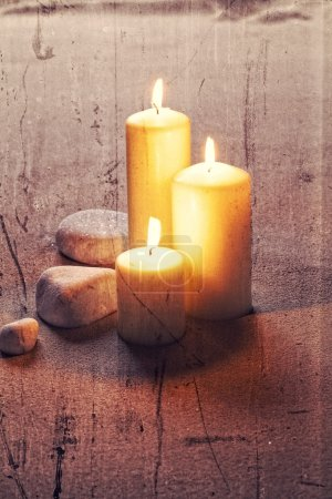 textured zen still life on sand with big lighted candles and white stones for retro effect