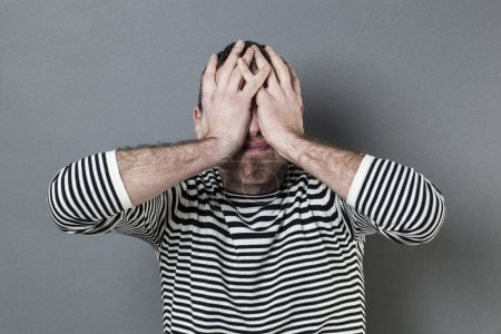 Photo for Mistake concept - disturbed middle age man with striped sweater hiding his face for blindness expressing regret and disappointment - Royalty Free Image