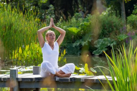 Photo pour Outdoors meditation - relaxed young yoga woman in praying lotus pose,closing eyes to relax and meditate on a wooden bridge with green foreground and water background, summer daylight - image libre de droit
