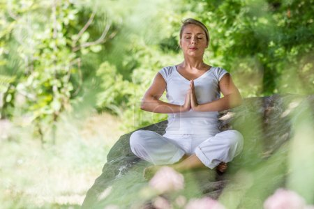 Photo for Outdoors meditation - young yoga woman exercising in lotus praying pose,closing eyes to focus on inner peace to relax and meditate on a big stone,green blurred foreground and background - Royalty Free Image