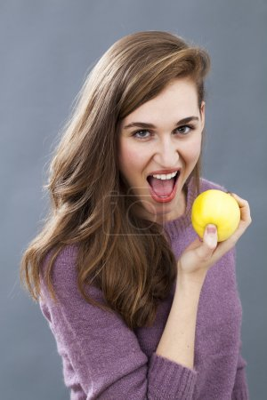 Photo for Diet and food concept - gorgeous young woman eating apple with appetite for healthy diet and good food - Royalty Free Image