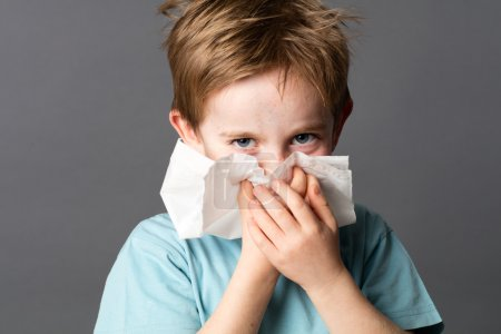 Healthcare learning - beautiful little boy with red hair using a tissue to clean his nose after a cold or having allergies, grey background studio