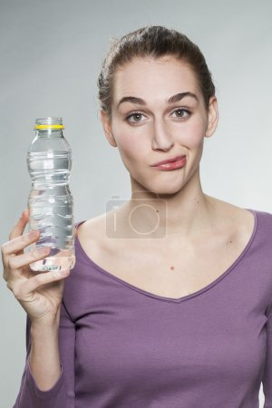 dubious 20s girl thinking twice before drinking zesty mineral water from bottle of water