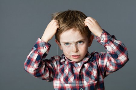 Annoyed young boy with freckles scratching his hair for head lice or allergies, grey background studi