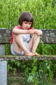 focused child playing with ivy leaves sitting alone in garden