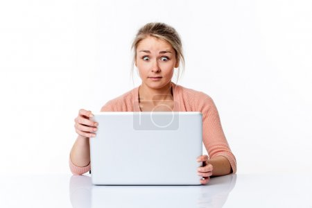 amazed young woman sitting at clean desk staring at computer