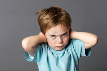 Stubborn little kid with red hair, freckles and an attitude ignoring parents scolding, blocking his ears with hands against education problems, grey background