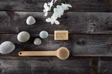 natural bath concept with pebbles, back brush and white orchids