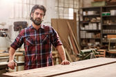 craftsman standing in workshop with heavy-duty machinery