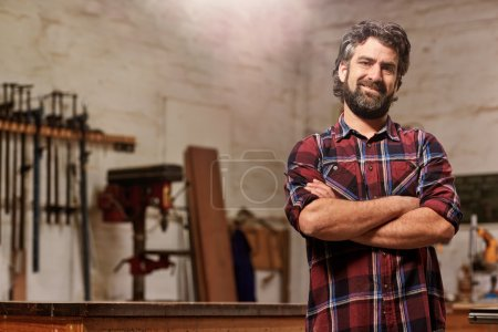 craftsman standing in workshop with arms folded