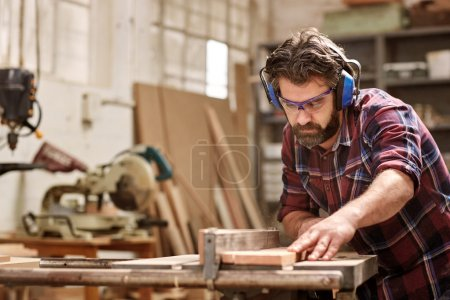 carpenter cutting piece of wood in workshop