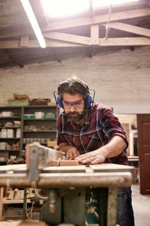 carpenter cutting piece of wood in workshop