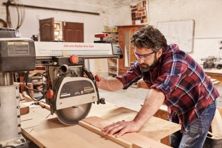 Carpenter cutting piece of wood with saw