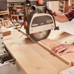 Skilled carpenter in his woodwork workshop, cuttin...