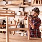 Artisan furniture designer and carpenter in his wo...