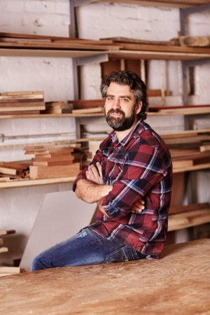 craftsman sitting in woodwork studio for portrait