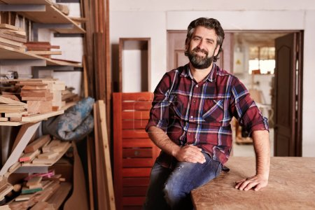 craftsman sitting in woodwork studio for portrait