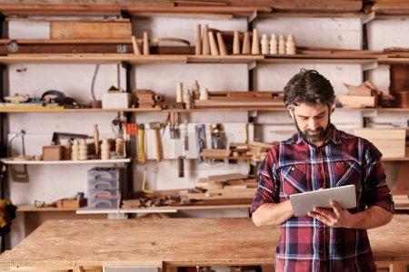 craftsman working on tablet in woodwork studio