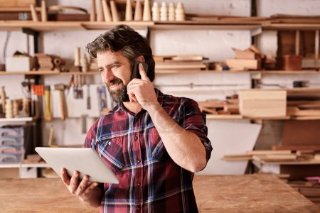 carpenter using mobile and holding tablet