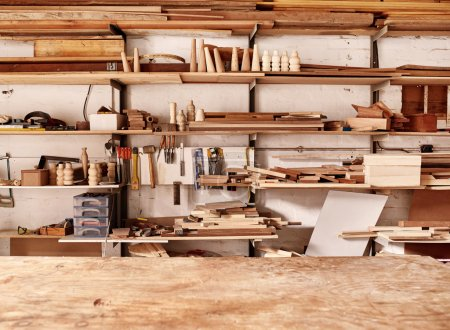 Photo for Woodwork workshop wall with many shelves holding a variety of wooden pieces and planks of wood, and some hand tools, with a wooden work bench in the foreground - Royalty Free Image