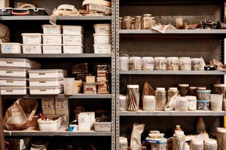 Foto de Estantes en un taller hecho de una unidad de metal, con una variedad de diferentes recipientes de plástico, frascos, cajas y suministros, dispuestos en grupos ordenados - Imagen libre de derechos