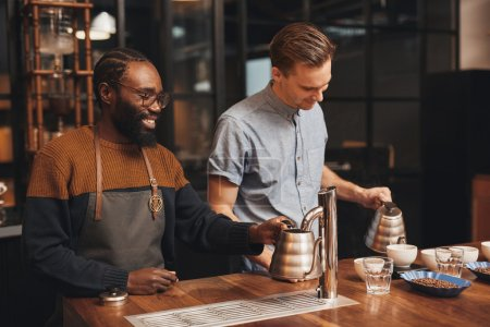 Baristas at wooden counter in modern roastery