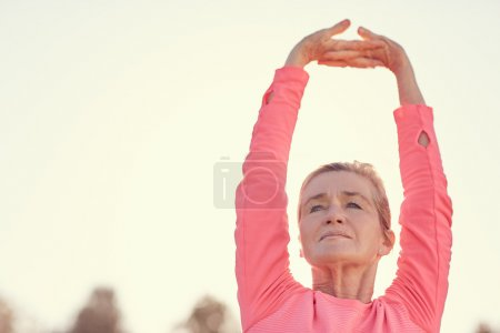 Photo for Senior woman in a pink sporty long sleeved top stretching her arms above her head, to warm up for some early morning exercise with gentle sunflare behind her - Royalty Free Image