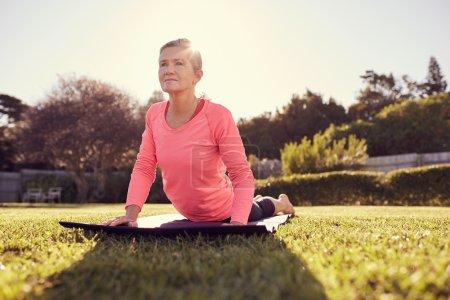 woman in cobra pose on yoga mat