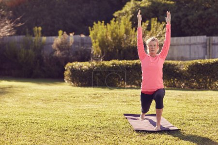 Senior woman in yoga warrior pose
