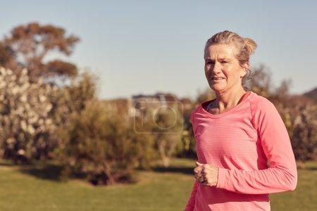 Athletic senior woman jogging outdoors