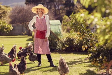 senior woman in backyard with chickens