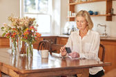 woman reading message on phone in kitchen