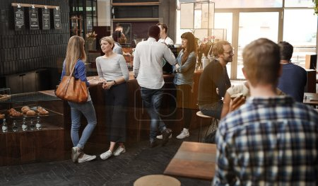 Photo for View through a window of a trendy modern coffee shop with some customers standing talking at the wooden counter, and other customers sitting at tables - Royalty Free Image