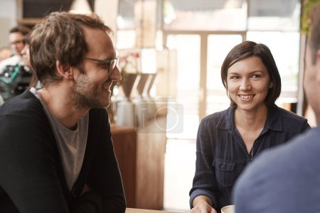 Woman sitting in modern cafe with friends