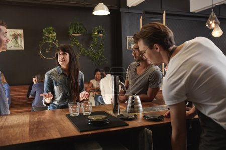 Woman chatting with colleagues at wooden counter